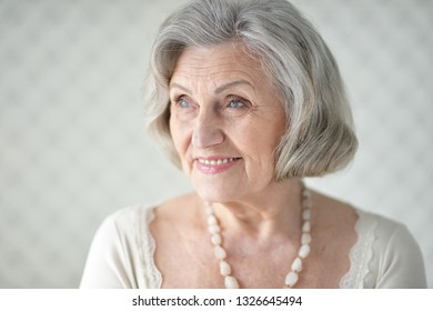 Portrait of cute happy senior woman posing at home