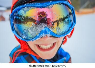 Portrait of Cute happy skier boy in a winter ski resort.
