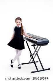 Portrait of cute happy smiling schoolgirl standing near electric piano - isolated on white.