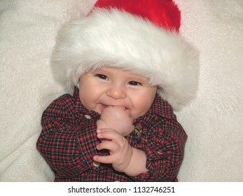 Portrait of a cute happy young baby sucking on his thumb wearing a Christmas Santa Claus hat and checkered shirt
