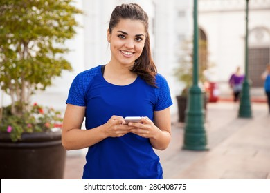 Portrait of a cute Hispanic female runner checking her cell phone before doing some exercise in the city