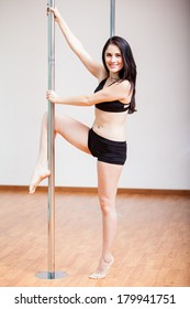 Portrait of a cute Hispanic pole fitness student during practice