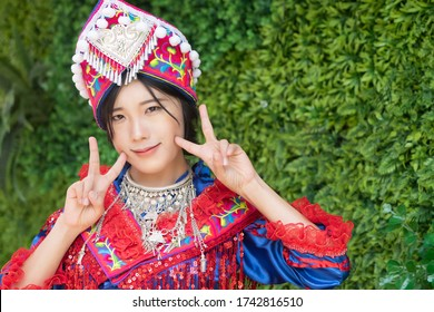 portrait of cute Hmong girl in tradition Hmong woman costume; Asian ethnic tribal people in traditional colorful clothing culture of Hmong or Miao people in east Asia and southeast Asia