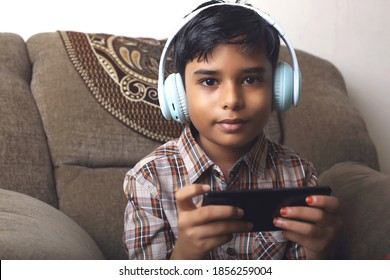 Portrait of cute Indian little boy using mobile phone while studying at home, remote education concept