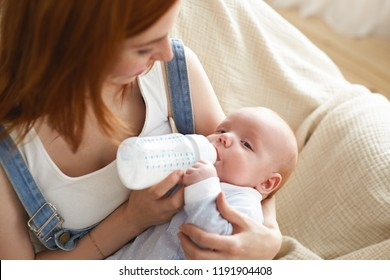 Portrait of cute infant resting in mother's arms, sucking on formula or expressed breast milk from glass nursing bottle. Tender young mom feeding her cute newborn child on couch in living room