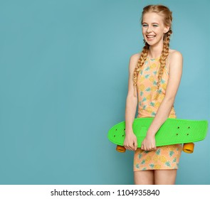 Portrait of cute joyful girl with amazing smile in short colorful summer dress. Joyous blonde with beautiful pigtails posing at studio. Isolated on blue background