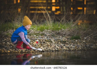 Portrait of cute kid boy playing with handmade ship. kindergarten boy sailing a toy boat by the waters' edge in the park.