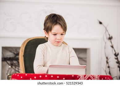 Portrait of cute kid boy sitting on green chair and playing with computer tablet during Christmas time. Holidays seasons.