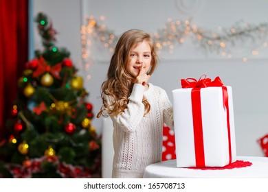 Portrait of cute kid girl holding big Christmas gift box