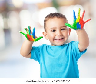 portrait of cute kid having fun with hands paint