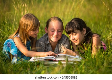Portrait of cute kids reading book in natural environment together.