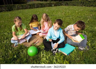 Portrait of cute kids reading books and drawing in park together