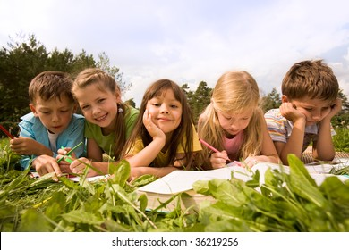 Portrait of cute kids reading books and drawing in natural environment together