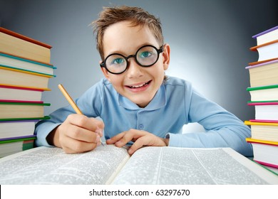 Portrait of cute lad in eyeglasses making notes in book during reading
