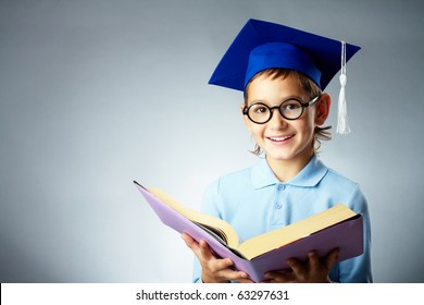 Portrait of cute lad in eyeglasses and student hat holding open book