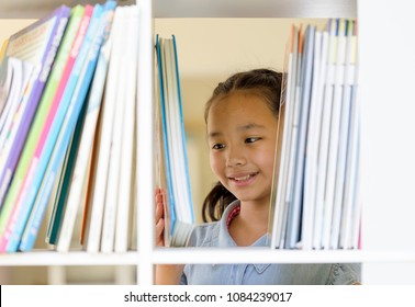 portrait of a cute little 10 year old girl. Asian Children choosing a book in the library. Happy smiley kids or pupils looking at the books. education,creativity and Promotion of reading concept.