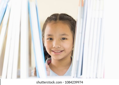 portrait of a cute little 10 year old girl. Asian Children choosing a book in the library. Happy smiley kids looking camera. education,creativity and Promotion of reading concept.