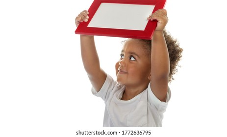 Portrait of a Cute Little African American Boy with Red Frame in Hands. Isolated on White Background. Photo with Copy Space. Preschool Education. Back to School Concept.