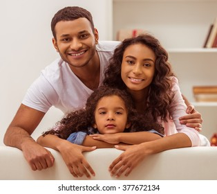 Portrait of cute little Afro-American girl and her beautiful young parents posing, looking at camera and smiling.
