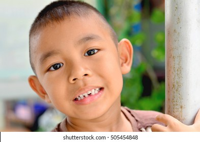 Portrait of a cute little Asia boy smiling broken tooth.