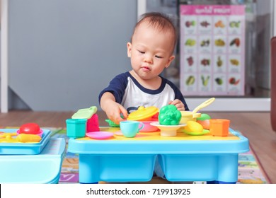 Portrait of Cute little Asian 18 months / 1 year old toddler baby boy child having fun playing alone with cooking toys in living room at home, Educational toys for young children concept
