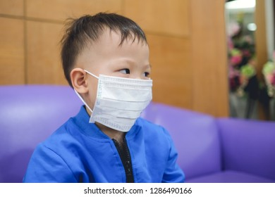 Portrait of cute little Asian 2 -3 years old toddler baby boy child wearing protective medical mask, Kid sitting on sofa waiting to see doctor in a doctor's clinic  / hospital - soft & selective focus