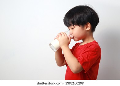 Portrait of cute little asian boy drinking milk. Isolated against light background.