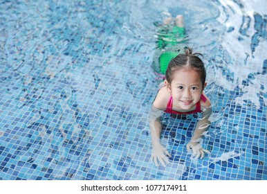 Portrait of cute little Asian child girl wear mermaid swimming suit has fun at the pool.