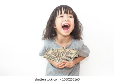 Portrait of cute little asian girl holding money isolated on white background. Small toddler asian girl counting her allowance dollar note.