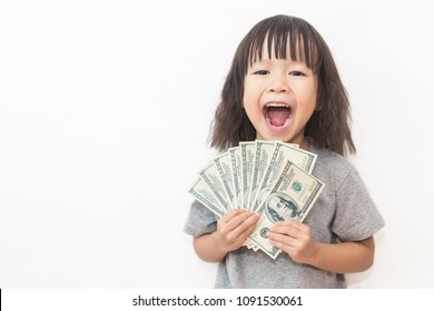 Portrait of cute little asian girl holding money isolated on white background. Small happy asian toddler girl counting allowance dollar note bill. Young entrepreneur child  successful concept