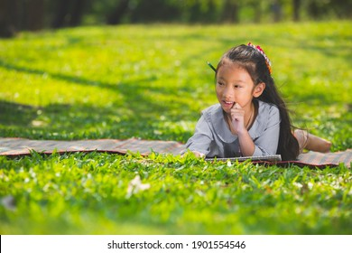 Portrait cute little asian girl lying on green grass with sketch book learning in park