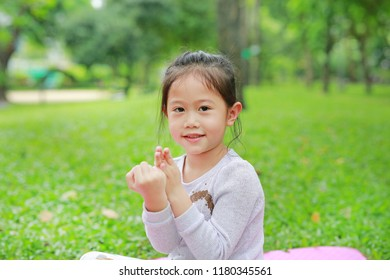 Portrait of cute little Asian kid girl sitting in the green garden with hands posture.