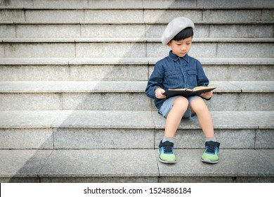 Portrait of a cute little asian schoolboy  in stylish outfit with beret sitting on a stairs in front of a library concentration reading a story book. Child's Brain Development, Cognitive Skills.