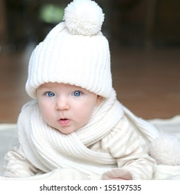Portrait of cute little baby with big beautiful blue eyes laying on blanket wearing cozy warm white knitted hat and scarf