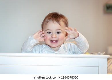 Portrait of a cute little baby boy at home in the crib making faces, sweet child having fun in his bedroom, happy healthy childhood