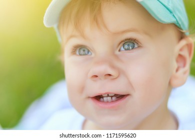 Portrait of a cute little baby boy with blue eyes in a sunny glow who has a smile has several teeth and charismatic emotions