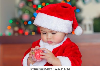 Portrait of a cute little baby boy with interest exploring Christmas tree bauble, adorable child dressed in red Santa costume celebrating Christmas at home