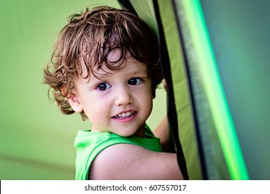 Portrait of cute little baby boy having fun outside. Smiling happy child playing outdoors camping