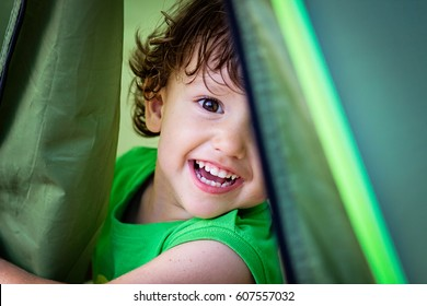 Portrait of cute little baby boy having fun outside hiding in a tent. Smiling happy child playing outdoors camping