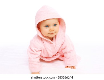 Portrait of cute little baby crawls in the pink bathrobe