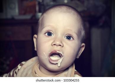 Portrait of a cute little baby eat porridge.