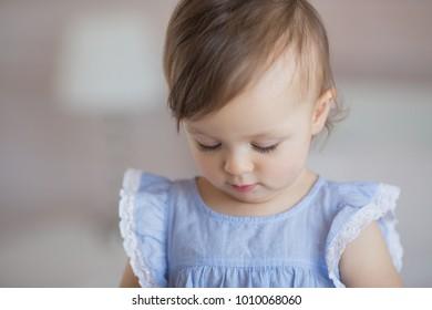 Portrait of a cute little baby girl in a blue dress looks down