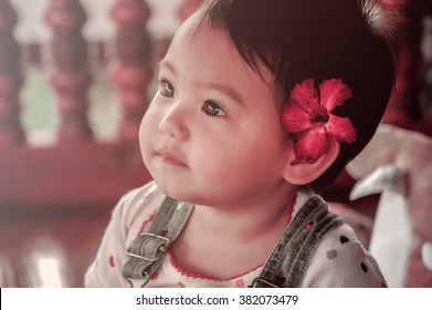 Portrait of a cute little baby girl with flower over ear, vinatge filtered tone