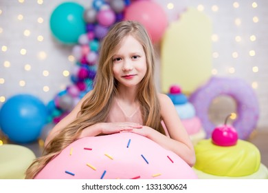 portrait of cute little blond girl with huge donuts and cupcakes
