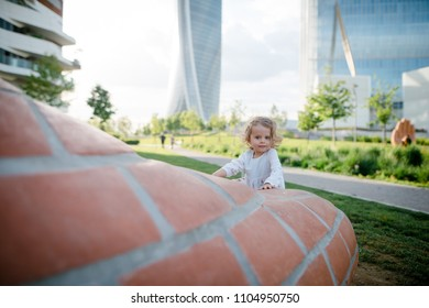 Portrait of cute little blonde girl with curly hair playing in the green city park near the modern skycrapers on sunny summer day