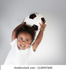 Portrait of a cute little boy with the ball, adorable small goalkeeper with soccer ball in hands over clear background, happy active childhood