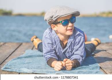 Portrait of a cute little boy with a cap and sunglases, lying by the river and enjoy the beautiful and sunny day
