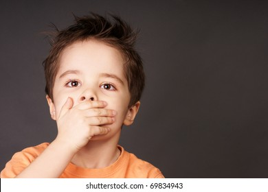 Portrait of cute little boy closed mouth with his hand, studio shot