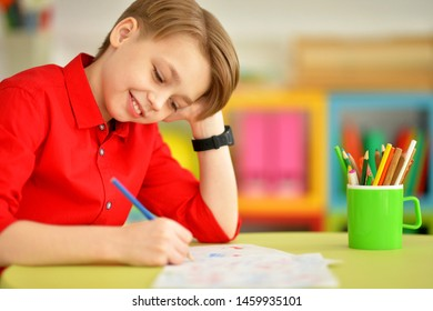 Portrait of cute little boy drawing with pencils