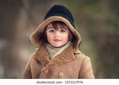 Portrait of a cute little boy in earflap hat. Image with selective focus and toning.